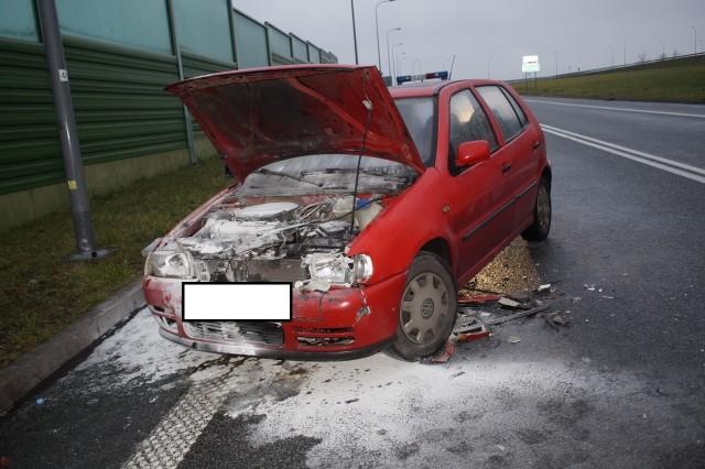 Kierująca VW Polo kobieta, uderzyła w tył jadącego przed nią kierującym BMW. Uderzenie w tył spowodowało zapalenie się komory silnika w VW. Musiała interweniować straż pożarna, która bardzo szybko ugasiła pożar samochodu.