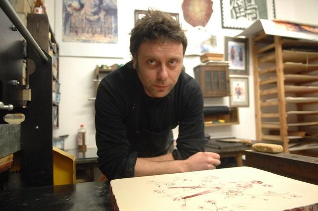 """Mariusz Kaczmarek to jeden z uczestników pleneru """"Kamień na kamieniu"""". Na co dzień prowadzi pracownię plastyczną Meszuge, w której w marcu artyści tworzyli swoje prace. Na zdjęciu przy prasie litograficznej."""