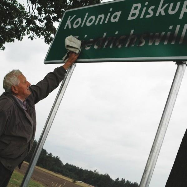 Zniszczona tablica przy wjeździe do Kolonii Biskupskiej.