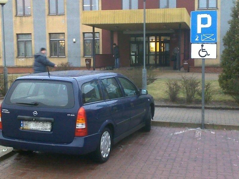 Opel zaparkowany na miejscu dla osoby niepełnosprawnej.