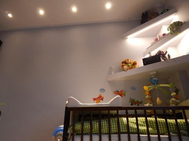 Oświetlenie pokoju dziecięcegoNad łóżeczkiem niemowlęcia przyda się dodatkowe oświetlenie. Tutaj: punkty LED oświetlające przewijak i ledowa taśma przyklejona pod półką.