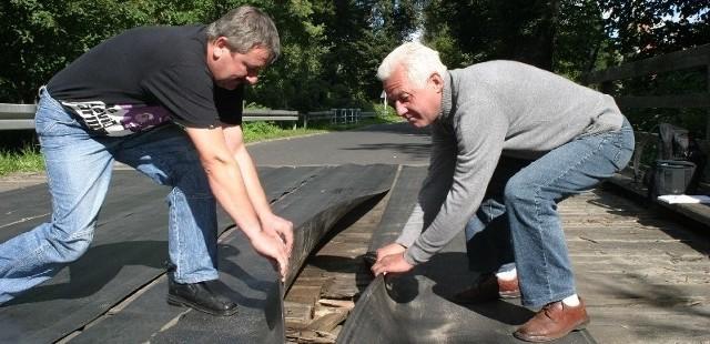 Tadeusz Biarda (z lewej) i Zbigniwe Wojtaluk odchylają stare, gumowe pasy transmisyjne, którymi wyłożono mosty. Widać pod nimi, że deski są spróchniałe, w niektórych miejscach an wylot.