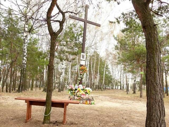 Przy krzyżu stanęła ławeczka, przywiązana łańcuchem do drzewa.