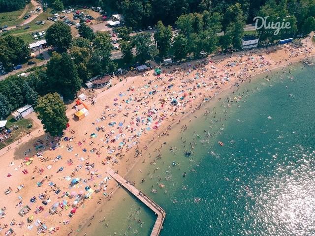 Na plaży w Długiem za 80 tys. zł powstaje minikompleks sportowo - wypoczynkowy. Ale to nie koniec nowości. Jeszcze w kwietniu - przed sezonem - zmieni się administrator kąpieliska.Do lata jeszcze daleko,  nocami zdarza się jeszcze przymrozek. Pomimo tego na najdłuższej plaży w regionie - w Długiem - powstaje OSA, czyli Otwarta Strefa Aktywności.Połowa z dotacji- Będzie tutaj plac zabaw, mała siłownia i stół do tenisa stołowego. Zamontowane zostaną ławki, kosze, całość będzie ogrodzona. Nie zabraknie też zieleni - wylicza burmistrz Strzelec Mateusz Feder. Taka plażowa atrakcja kosztuje 80 tys. zł, ale połowę tej kwoty stanowi dotacja z budżetu państwa. Na pewno prace zakończą się jeszcze przed sezonem, który - jak zawsze - ma się rozpocząć pod koniec czerwca. Jednak OSA nie będzie na Długiem jedyną nowością w te wakacje. Zmieni się też administrator obleganego kąpieliska. Wstęp wciąż za darmoPrzez ostatnie lata nadzorcą plaży było gorzowskie Stowarzyszenie Pomocy Bliźniemu im. Brata Krystyna (na miejscu ma bazę kolonijną, przez to pracownikom stowarzyszenia łatwiej było doglądać terenu cały rok). Jeszcze w kwietniu teren przejmie jednak strzeleckie Przedsiębiorstwo Gospodarki Komunalnej. Bez obaw: wstęp na plażę pozostanie bezpłatny (w przeciwieństwie do parkingów - za nie wciąż trzeba będzie płacić). Szykujcie się na zabawę!Już wiadomo, że 27 lipca na jeziorem odbędzie  się kolejna edycja imprezy Disco Długie Festival. Gwiazdę zabawy już przedstawiono: będzie to zespół Piękni i Młodzi.Zobacz wideo: Spływ Obrą to wspaniała przygoda