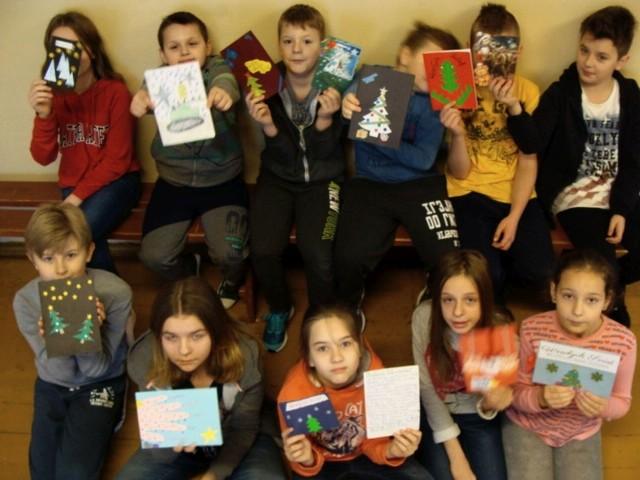 Dzieci ze szkoły w Sorbinie prezentują własnoręcznie wykonane kartki świąteczne dla żołnierzy.