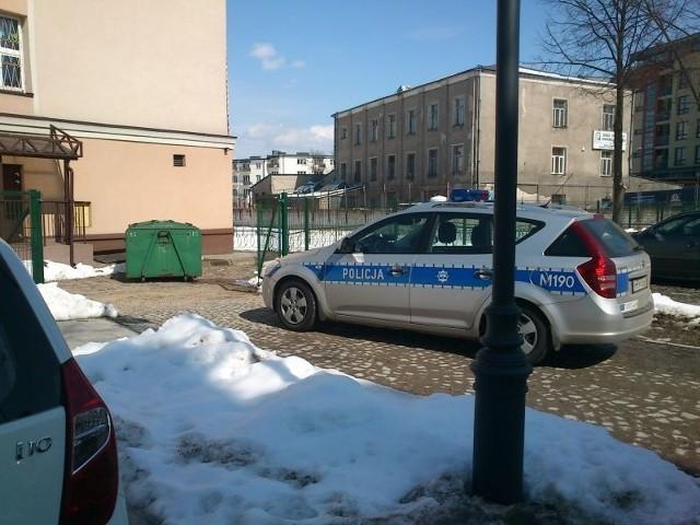 Radiowóz bez kierowcy, zaparkowany we wjeździe na teren szkoły.