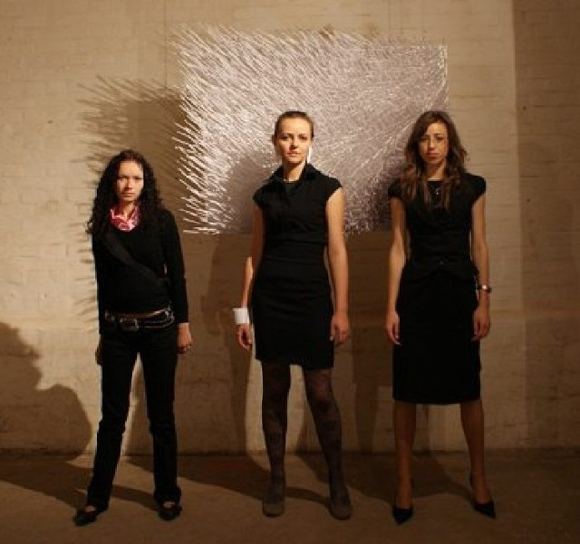 """Kamila Tkacz (w środku) z przyjaciółkami na tle swojej pracy """"PoZa"""", której motywem przewodnim jest gra światła i cienia."""