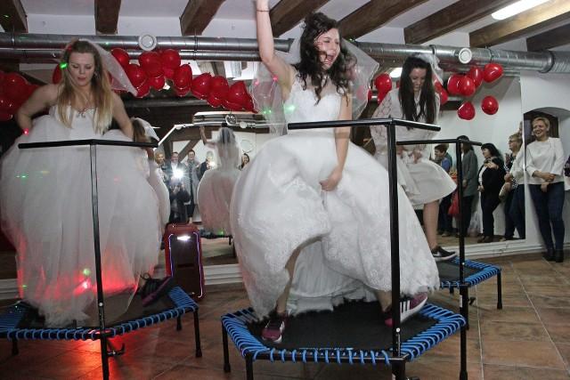 """W Grudziądzu otwarto nowy fitness club  """"Faktor Fit"""". Na jego uroczyste otwarcie przygotowano szereg niespodzianek. Jedną z nich była """"bitwa"""" ćwiczących oraz skoki na trampolinach w... sukniach ślubnych."""