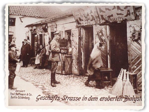 Przy białostockim Ratuszu. Niemiecki oficer kpiąco wskazuje na zastraszoną kobietę.