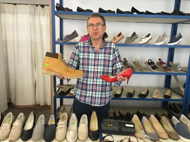 Janusz Karbowiak pokazuje męskie buty w rozm. 50 i damskie szpilki w rozm. 44