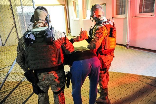 Lubuscy policjanci zatrzymali 30-letniego mężczyznę, który uciekł z konwoju do szpitala przy ul. Walczaka w Gorzowie. W obławie wzięło udział ponad 260 policjantów z całego województwa.W piątek, 21 kwietnia, około północy policja zatrzymała mężczyznę, który zbiegł z policyjnego konwoju w Gorzowie. - 30-latek został zatrzymany przed północą w Drezdenku przez miejscowych policjantów - mówi nadkom. Marcin Maludy, rzecznik lubuskiej policji.Kluczowa okazała się informacja od kobiety, która zauważyła mężczyznę odpowiadającemu rysopisowi. Utrzymywała ona łączność z dyżurnym, przekazując precyzyjną relację o pozycji zbiega. Podczas zatrzymania mężczyzna był zaskoczony i nie stawiał oporu. Policjanci dziękują internautom za udostępnianie na portalach społecznościowych zdjęcia i informacji o poszukiwanym. Do ucieczki doszło w piątek, 20 kwietnia, po godz. 12. Mężczyzna przewożony był na badania do gorzowskiego szpitala. Podczas jazdy oswobodził się z kajdanek założonych na ręce i nogi. Gdy radiowóz zatrzymał się przy szpitalu i policjanci otworzyli drzwi, 30-latek uciekł w kierunku ogródków działkowych. Funkcjonariusze natychmiast rozpoczęli pościg, oddając strzały ostrzegawcze. Lubuska policja rozpoczęła akcję poszukiwawczą zakrojoną na szeroką skalę. Wzięło w niej udział ponad 260 policjantów, wyszkolone psy oraz śmigłowiec. Liczył się czas, bo uciekinier mógł być bardzo niebezpieczny. 30-letni mieszkaniec Sulęcina jest podejrzany o morderstwo 78-letniej kobiety. W lutym tego roku miał skrępować kobietę w jej mieszkaniu i ją okraść. Brutalne traktowanie ofiary i zaklejenie jej ust taśmą spowodowało, że kobieta zmarła. Zatrzymany to recydywista. Odsiedział już siedem lat w więzieniu.Na razie nie wiadomo, w jaki sposób mężczyzna wyswobodził się z kajdanek. - Szczegółowym ustaleniem wszelkich okoliczności związanych z zachowaniem się policjantów odpowiedzialnych za konwojowanie zatrzymanego, zajmują się specjaliści z Wydziału Kontroli Komendy Wojewódzkiej Policji w Gorzowie W