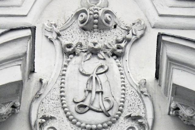 Kamienicę  przy ul. Sienkiewicza 14 zbudował Abram Łapidus. To jego inicjały znajdują się w kartuszu na szczycie fasady.