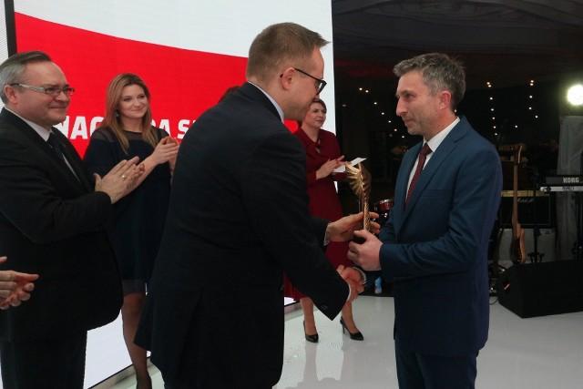 Wiceminister Inwestycji i Rozwoju, Artur Soboń wręcza statuetkę Piotrowi Tomali, himalaiście z Lublina, uczestnikowi zimowej wyprawy na K2