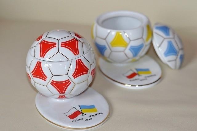 Pamiątka z Ćmielowa to niewielka porcelanowa piłka z otwieranym denkiem i podstawką, na której wymalowane są flagi organizatorów Mistrzostw EURO 2012.