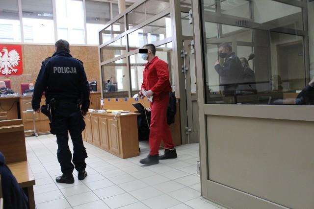 Jacek W. ps. Małpa na sali rozpraw krakowskiego sądu. Jest skuty łańcuchami i pilnowany przez policjantów uzbrojonych  broń maszynową. Jego oskarżenie było możliwe dopiero po ekstradycji z Wielkiej Brytanii, gdzie się ukrył przed polską policją i prokuraturą