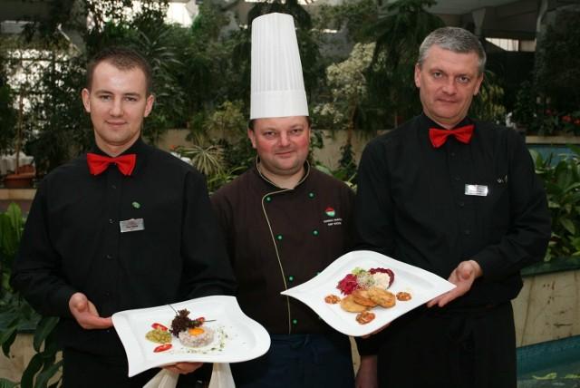 """Kelner Piotr Sobaś, szef kuchni kieleckiej restauracji Patio Konrad Marcisz oraz kelner Dariusz Rokita prezentują potrawy, które znajdą się w książce kucharskiej """"Świętokrzyskie smaki""""."""