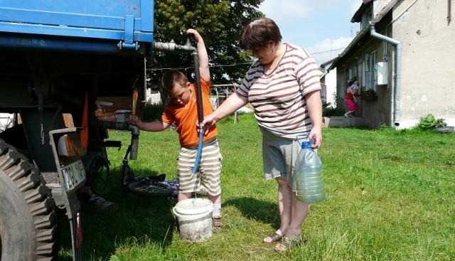 W domu Władysławy Kipior mieszkają cztery osoby, więc jeden baniak z wodą na cały dzień nie wystarczy. - Trochę trzeba się nadźwigać, ale daję radę - mówi pani Władysława. Po wodę z beczkowozu przyszła z wnuczkiem Hubertem.