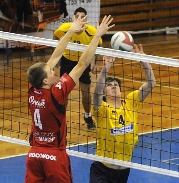 Piłkę wystawia rozgrywający Olimpii Konrad Krzywiecki, do bloku wyskoczył przyjmujący Oriona Miłosz Olejniczak. W tle atakujący sulęcinian Patryk Wojtysiak.