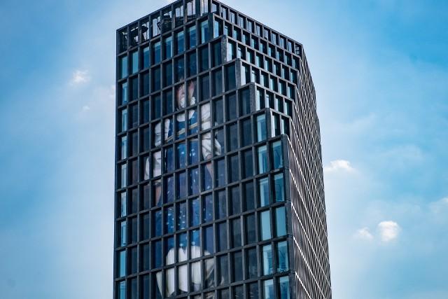 Poznański biurowiec Bałtyk został obklejony wielkoformatowym wydrukiem kadru filmowego: uwięzionej artystki, jako kobiecej bajkowej postaci z kneblem w ustach. Zagospodarowana przestrzeń obejmie ponad 600 mkw. elewacji.