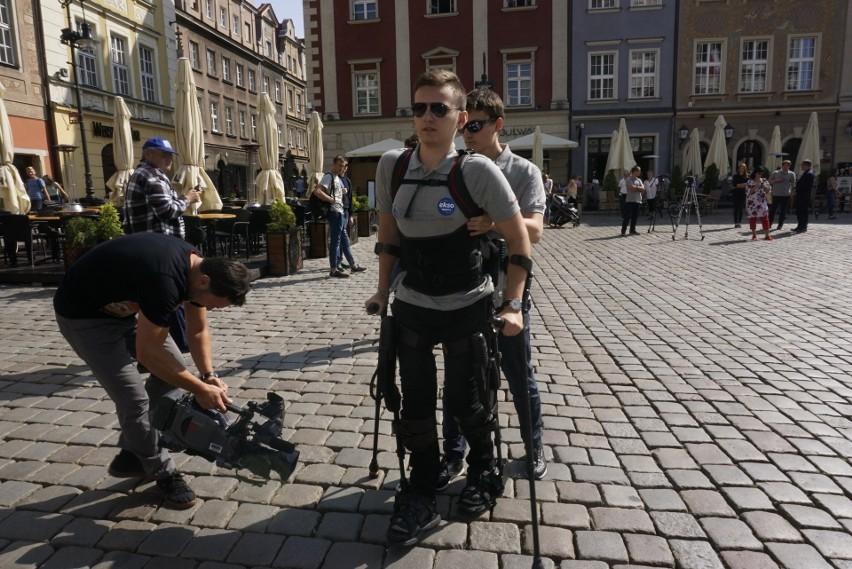 """Akcja """"Michał idzie przez Polskę"""": 17-latek z urazem rdzenia kręgowego za pomocą ezgoszkieletu spacerował po poznańskim Starym Rynku"""