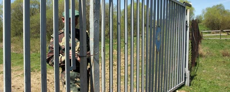 Ukraiński pogranicznik zamyka bramę na drodze, która ma w przyszłości prowadzić do przejścia granicznego Boberka-Smolnik.