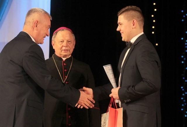 Hubert Banasik, Wolontariusz Roku 2018, przyjmuje życzenia  od księdza Andrzeja Tuszyńskiego i biskupa Henryka Tomasika.