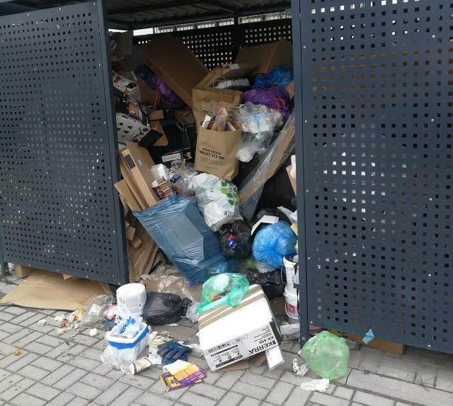 Mieszkaniec osiedla przekonuje, że śmieci nie były odbierane od miesiąca i pokazuje zdjęcia z dwóch wiat śmietnikowych