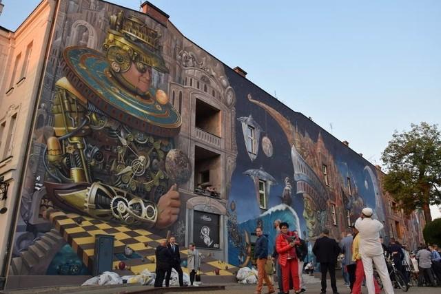 CZĘSTOCHOWA. Na południowej ścianie kamienicy przy al. Wolności 19 mural Strażnik Czasu. To dzieło znanego częstochowskiego zegarmistrza Stefana Rybickiego (pomysłodawca) i znanego częstochowskiego artysty Tomasza Sętowskiego (projekt, wykonanie).
