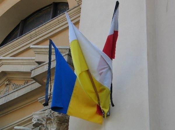 Polska, ukraińska i papieska flaga wiszą na wspólnych uchwytach na murze katedry greckokatolickiej w Przemyślu.