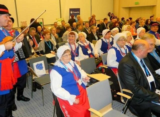 """Wśród uczestników konferencji był ludowy zespół """"Łochowianie"""". W tle widać panie w tradycyjnych strojach kujawskich"""