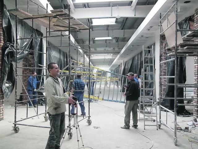 Na pierwszym planie Dariusz Rental z firmy Aplauz. Laserem mierzy poziomy ścian, by położyć regipsy (fot. Michał Szczęch)