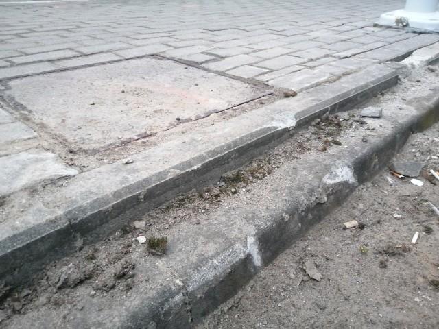 Tak parking wygląda po zakończeniu prac przy instalacji słupa i kamery. Pokruszone płyty i krawężniki, otwory w płytach zasypane betonem i błoto...