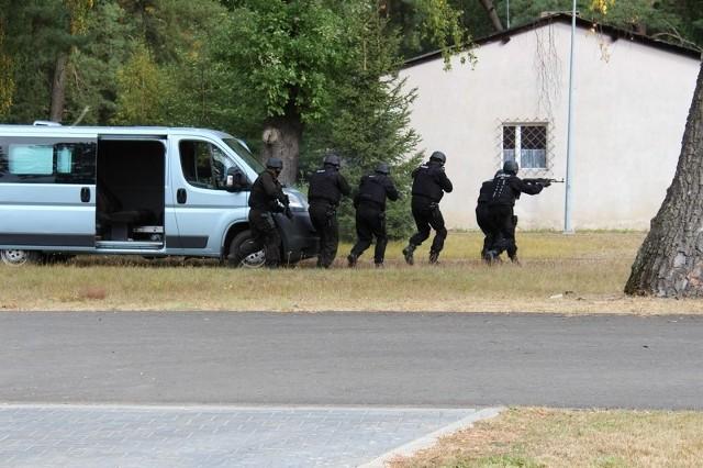 Policjanci wraz ze służbami ratowniczymi ćwiczyli w Wędrzynie. Na terenie jednostki wojskowej funkcjonariusze zatrzymali włamywacza. Niezbędny był udział antyterrorystów, którzy musieli ścigać uzbrojonego wartownika.Na terenie jednostki wojskowej w Wędrzynie według opracowanego scenariusza przeprowadzono ćwiczenia, które miały na celu skoordynowanie działań różnych służb ratowniczych. W akcji wzięli udział policjanci z Sulęcina, antyterroryści z Gorzowa Wlkp., żandarmeria wojskowa w Wędrzynie oraz pracownicy oddziału wart cywilnych w Wędrzynie.W tym celu zainicjowano kradzież z włamaniem do pomieszczenia magazynowego należącego do jednostki wojskowej w Wędrzynie. Sprawcy biorący udział w tym zdarzeniu zostali spłoszeni przez jednego z pracowników, po czym oddalili się w rejon pobliskich zabudowań. W trakcie poszukiwań za sprawcami kradzieży policjanci wspólnie z funkcjonariuszami żandarmerii wojskowej ustalili ich miejsce ukrycia się. Przy zatrzymaniu uzbrojonych sprawców wykorzystani zostali antyterroryści.Podczas zatrzymania mężczyzn okazuje się, że na teren wojskowy wpuścił ich zaprzyjaźniony wartownik. Informacja o zatrzymaniu sprawców dociera do współpracującego z nimi wartownika. Ten w obawie o konsekwencje ucieka z terenu ochranianego do pobliskiego lasu zabierając ze sobą broń służbową. Policjanci z Sulęcina wspólnie z funkcjonariuszami żandarmerii przystępują do działań pościgowych za uzbrojonym wartownikiem. Podczas penetracji terenu leśnego zatrzymują mężczyznę.Dzięki przeprowadzonym ćwiczeniom, w sytuacji realnego zagrożenia takie współdziałanie pozwala na doskonalenie i koordynowanie poszczególnych służb, których celem jest bezpieczeństwo i ratowanie życia.