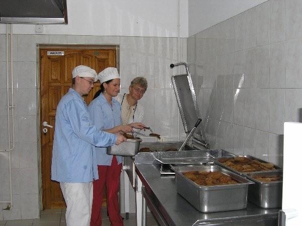 Wczoraj na obiad w stołówce Caritasu był kotlet  mielony z ziemniakami. Na zdjęciu: Anna  Dąbrowska, kucharka i Marek Dudziński,  poborowy odbywający w Caritasie zastępczą  służbę wojskową. Zgodność posiłków z  recepturą sprawdza codziennie Zenobia  Kujaczyńska, kierownik zaopatrzenia.