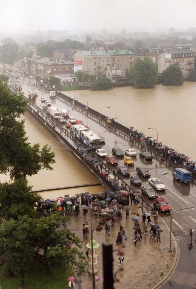 """W lipcu 1997 roku przez Polskę przeszła """"Powódź Tysiąclecia"""". Drugi tydzień lipca w roku 1997 przebiegał w południowej Polsce pod znakiem ciągle padającego obfitego deszczu. Kilkudniowe  opady doprowadziły szybko do podniesienia się poziomów rzek, także w Małopolsce. W trakcie powodzi w Polsce zginęło 56 osób, szkody oszacowano na około 3,5 miliarda dolarów. Jak wyglądała walka z żywiołem w Krakowie i innych małopolskich miejscowościach? Jakich szkód dokonała wielka woda? Zapraszamy do obejrzenia zdjęć z naszego archiwum."""