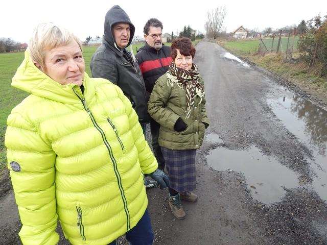 - Droga po naprawie wytrzymała ledwie kilka dni. Znów potworzyły się tu dziury i kałuże - mówią (od lewej): Halina, Krzysztof i Waldemar Kopciowie oraz Zofia Bibrowicz, mieszkańcy ul. Skrajnej.