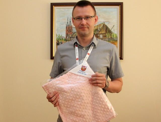 Nowi mali obywatele gminy otrzymują prezent: kocyk z logo gminy