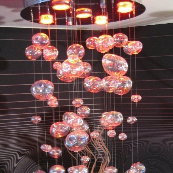 Diody świecą u góry żyrandola, a światło odbija się  w szklanych kulach różnej wielkości.