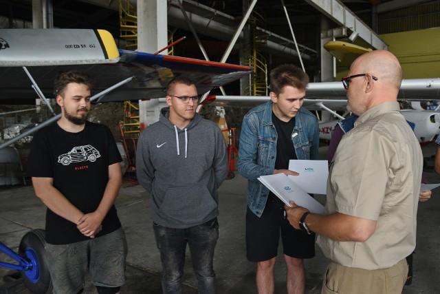 Dr J. Gniazdowski wręcza studentom Wydziału Mechanicznego vouchery na lot szybowcem w podziękowaniu za zaangażowanie w działalność organizacyjną na rzecz Wydziału.