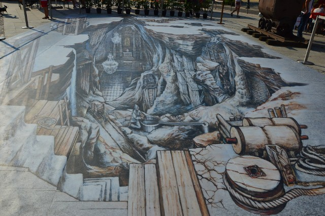 """Na Rynku Górnym w Wieliczce powstała kompozycja anamofriczna 3D """"Solny Świat 2021. W porównaniu do trójwymiarowego malowidła """"Solny Świat"""", odsłoniętego tu w czerwcu 2012 roku, nowy obraz jest mniejszy (nie obejmuje już rzeźb górników) i wykonany inną techniką"""