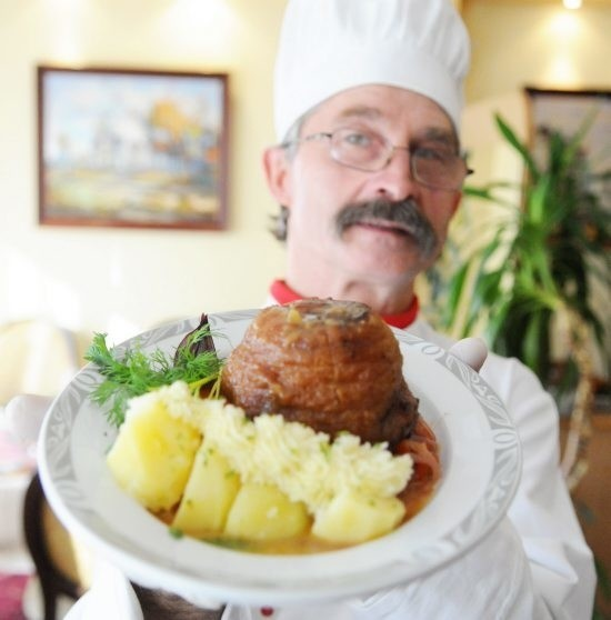 Jan Stodulski prezentuje golonkę z czerwoną cebulą i papryką. Zapewnia, że inne golonkowe dania są co najmniej tak samo smaczne.