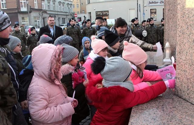 """W 152. rocznicę urodzin marszałka Józefa Piłsudskiego dzieci ze Szkoły Podstawowej nr 5 i młodzież z klas mundurowych III LO  z historykiem Łukaszem Piaseckim zorganizowały uroczystość pod jego pomnikiem w Grudziądzu. Dzieci z """"piątki"""" deklamowały wierszyki i złożyły na pomniku własnoręcznie wykonane laurki."""