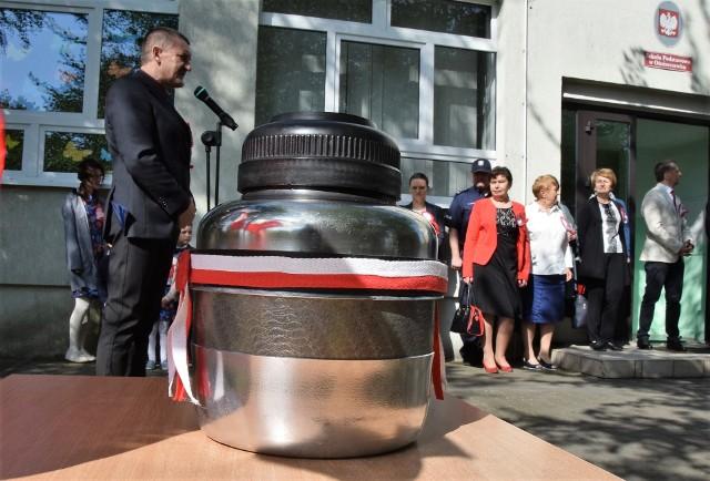 """Niecodzienna uroczystość miała miejsce w Szkole Podstawowej w Ośniszczewku. Z okazji 100-lecia odzyskania przez Polskę niepodległości, na szkolnym dziedzińcu wkopano kapsułę czasu. W jej wnętrzu umieszczono pierwsze strony gazet, widokówki prezentujące migawki z terenu gminy Dąbrowa Biskupia, folder reklamujący gminę, kilka monet, pendrive'a z piosenkami oraz ze zdjęciami i filmikami dokumentującymi życie szkoły. Znalazł się tam także telefon komórkowy, na który tuż przed zamknięciem w kapsule czasu uczestnicy uroczystości wysyłali sms-y z życzeniami dla Polski. Do kapsuły trafiły również listy z podpisami zaproszonych gości. Kiedy nastąpi otwarcie specjalnego pojemnika? Inicjatorzy wydarzenia, społeczność SP w Ośniszczewku, liczą na to, że stanie się to dokładnie za 100 lat. Uroczystość uświetnili przedszkolacy i uczniowie SP. Szczególnie wzruszający był występ najmłodszych artystów zatytułowany """"Kocham cię, Polsko""""."""