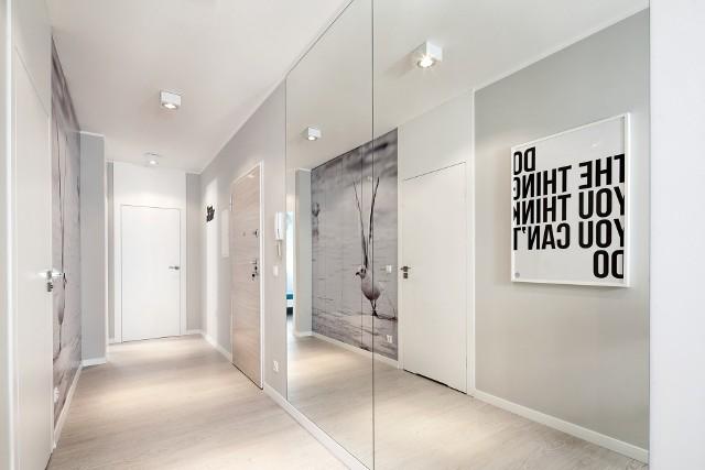 Projekt wąskiego przedpokojuWąskich i ciasnych pomieszczeń nie powinnyśmy zagracać. Pamiętajmy też, że jasne kolory i duże lustra optycznie powiększają przestrzeń. Świetnie widać to na tym przykładzie.
