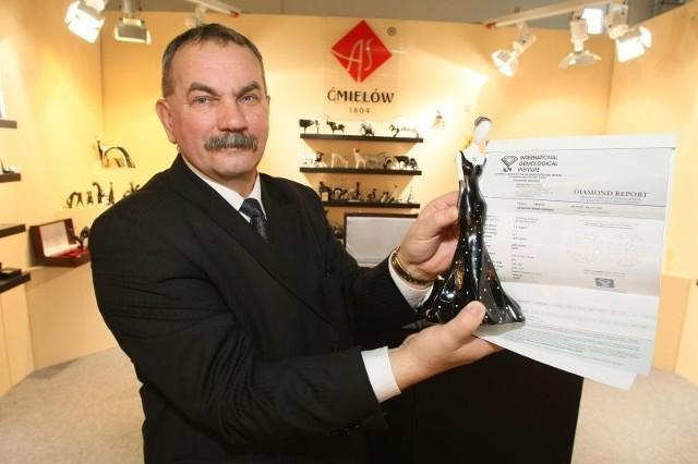 Adam Spała prezentuje figurkę wysadzaną diamentem na tle certyfikatu potwierdzającego jego autentyczność.