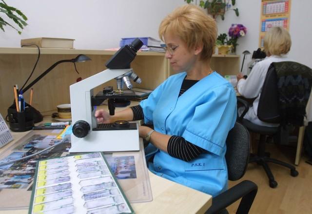 Anna Trojnar, cytotechnik, ocenia rozmaz cytologiczny.