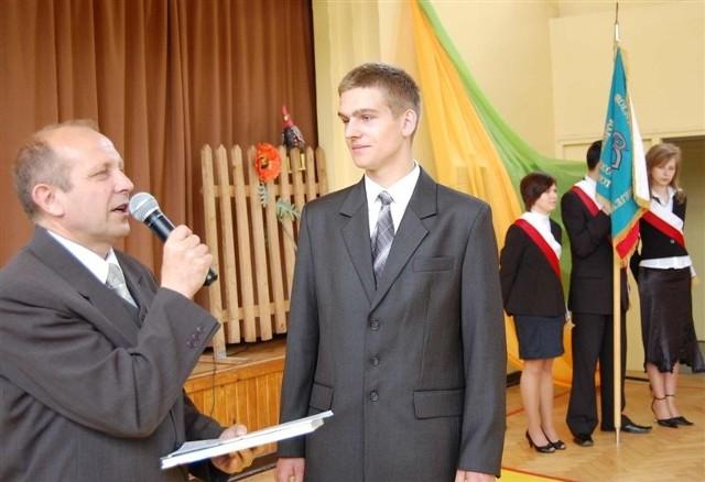 Emilian Dłuski jako prymus odbiera nagrodę z rąk dyrektora szkoły Tadeusza Budzisza.