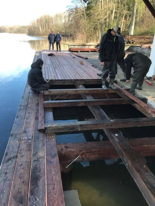 """Trwa budowa pomostu przy bosmance nad jeziorem Jeleń. Będzie miał kształt litery L o parametrach: długość  15,24 m i 17,94 m,  szerokość 3,73 m i 3,15 m. Pomost w całości wykonany z drewna modrzewiowego, mocowany za pomocą dębowych pali wbijanych w dno jeziora. Dodatkowo na pomoście zamontowane cumy do kotwienia oraz drabinka. Wykonawcą jest firma Wygocki z gm. Główczyce.<script async defer class=""""XlinkEmbedScript""""  data-width=""""640"""" data-height=""""360"""" data-url=""""//get.x-link.pl/e28f424d-c48e-9c6b-f757-c6eff7102ec0,a9a55f22-0329-03ce-9abb-e7056785fe45,embed.html"""" type=""""application/javascript"""" src=""""//prodxnews1blob.blob.core.windows.net/cdn/js/xlink-i.js?v1"""" ></script>"""