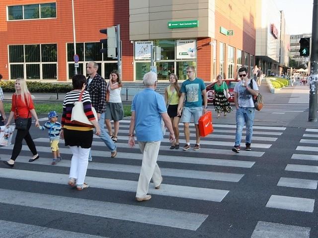 Piesi przechodzą przez ulicę na raty. Nie wszyscy chcą czekać na zielone światło i próbują przemknąć na czerwonym.