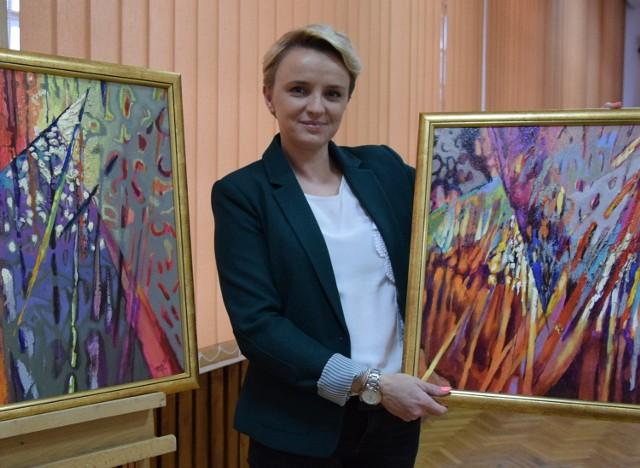 Kamila Dobrowolska z Miejsko – Gminnego Domu Kultury w Końskich prezentuje prace jednego z uczestników wystawy Michała Poręby